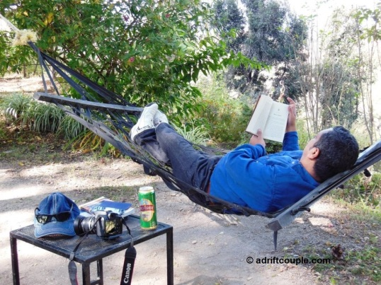 Relaxing in a hammock reading a book at Park Woods Shoghi.