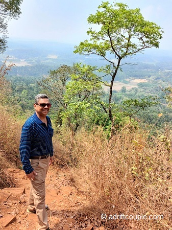 Climbing up the dusty route on Kurumbalakotta trek in Wayanad with green vistas below.